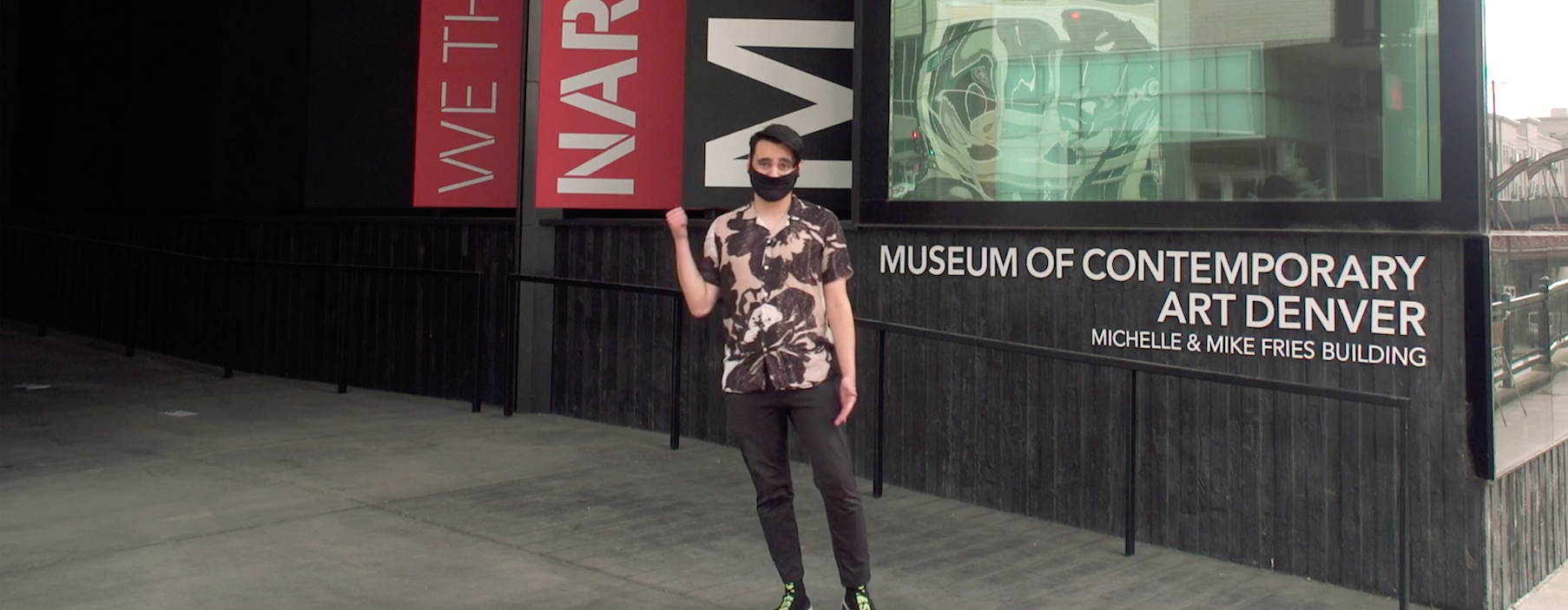 Image: Young man in a mask stands outside the museum and he stands in a printed shirt, black pants, and motions with his right hand to follow him.