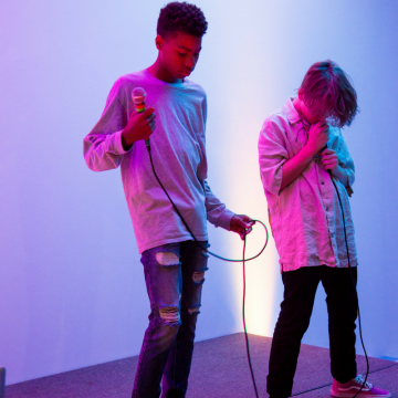 Two young men hold microphones and are lit by pink and blue lighting.