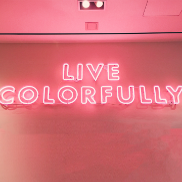 Pink neon light is hung upon a wall indoors reading Live Colorfully
