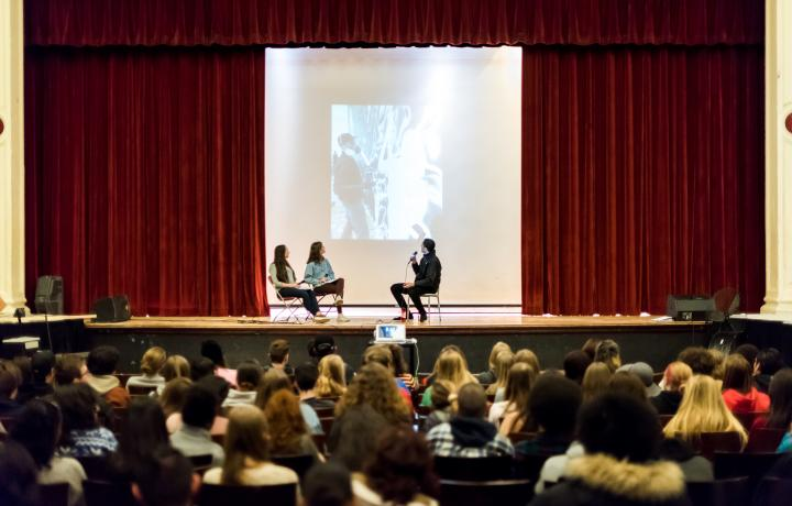 School auditorium, where students are seating in seats looking at a stage where two teen students are interviewing the artist Cleon Peterson