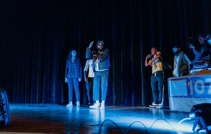 Hip hop performer, performing on a dark stage, lite by blue lights, while students dance and MCs listen with headphones in the background