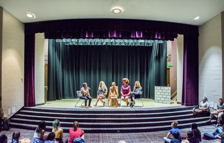 School stage, with a group of drag queens sitting on stage, holding mics, with students watching in the audience