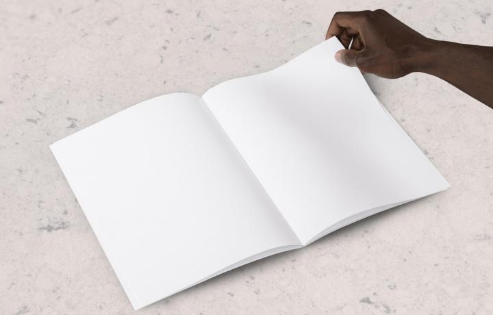 White notebook laid flat on table with hand turning the page