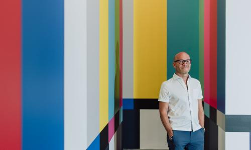 A portrait of former director Adam Lerner poses in front of a wall painted to resemble technicolor on a tv set. He is bald, wearing a white short sleeve button up, and blue chinos. He smiles gently.