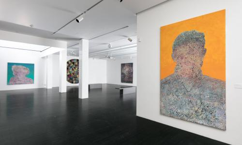 A gallery space filled with large paintings hanging on white walls. The artworks are abstract depictions of unidentifiable people. Almost like a silhouette.
