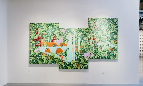 A three panel painting of green ferns with an abstract orange and white pattern superimposed on the leaves hangs on a white gallery wall