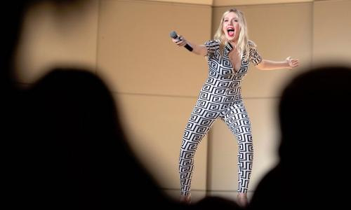 A blonde woman stands on stage in a black and white greco patterned body suit. She has her hand outstretched pointing a microphone towards the crowd.