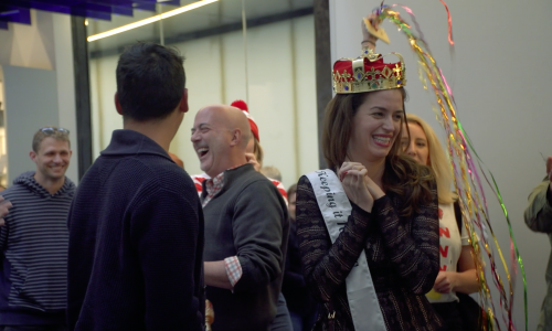 A man and a woman are surrounded by several people. The woman is wearing a white sash and a toy crown.