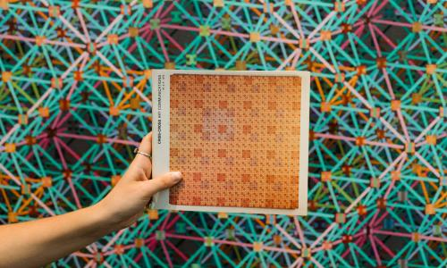 A hand holds a piece of paper with an abstract pattern in tan on it in front of an abstract geometrical artwork.