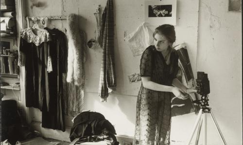 Candid shot in a sepia tone of a woman setting up a camera on a tripod. She is indoors and wearing a sheer dress. Behind her is a wall where clothes and photographs hand. The floor is cluttered with various belongings.
