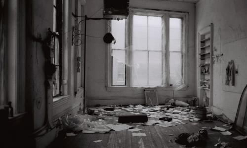 A black and white photo of a messy interior space. There is a window covered in transparent tarp at the far end of the room. Papers and other objects litter the floor.