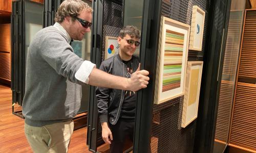 Two young men wearing color correcting glasses view an artwork in a gallery and are smiling brightly.
