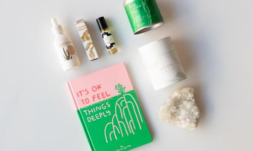 A hotpink and bright green book reads It's ok to feel things deeply; A white crystal rock; a vial of cbd drops from Dram. Green tea, jasmine, and sugar jems mix from Par Avion Tea; a white container reading moon bath; a scent roller from rootfoot.