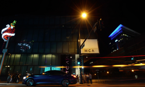 Exterior shot of the MCA Denver at night from street view. A heart sculpture is lit up and several people wait near the entrance in a line.