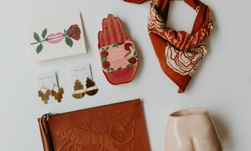"Seven objects on a blank white surface. A red ascot. A succulent potter in the shape of a persons buttocks. A leather pouch with an imprinted leopard. Two golden earrings. A postcard depicting a mouth biting a rose. A red hand with the text ""Everyday Offerings of Love."""