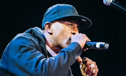 Photo of rapper Rakim rapping into the mic, with a ball cap and hoodie