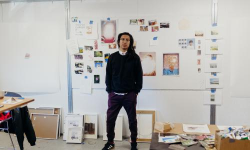 Image of George P. Perez in his studio standing in front of several artworks hung upon a white wall.