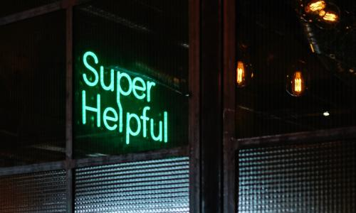 A green neon sign reads Super Helpful