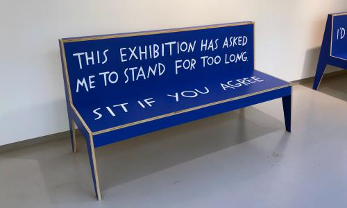 "A bright blue bench with white, hand-lettered text that reads, ""This exhibition has asked me to stand for too long. Sit if you agree"""