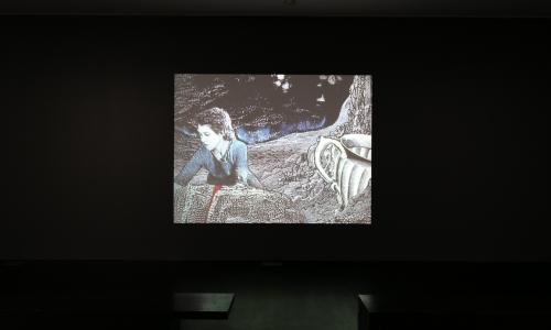 A stop motion film is projected onto a gallery wall. In it, a woman is looking through the ground in a rocky environment. It is half drawn with superimposed paper cutouts.