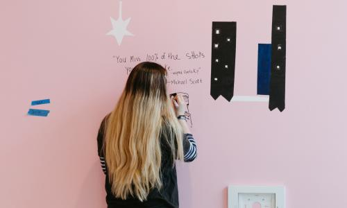 "A woman with ombre hair draws an image of a man on a pink wall. The text written in sharpie reads ""You miss 100% of the shots you don't take. -wayne Gretzky"" -Michael Scott"