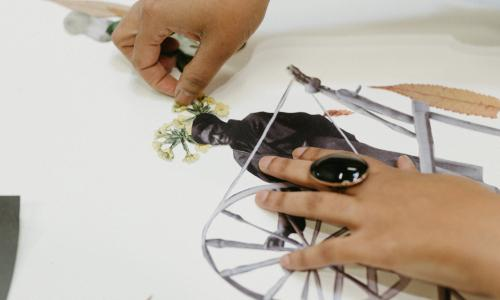 Close up image of Tya Anthony's hands working on a collage in her studio