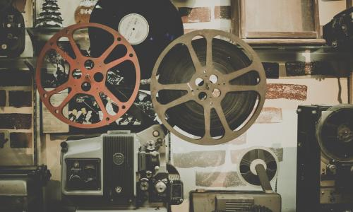 Film reels sit against a brick wall in a sepia tone.