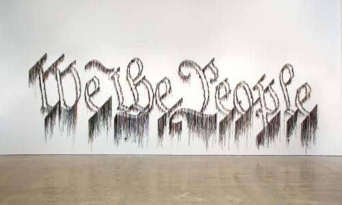 "The words ""We the People"" are spelt with string and attached to a white gallery wall."