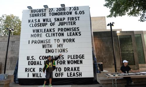 "A man stands in front of a large marquis with his arm outstretched. The marquis has several headlines from news sources that promise something to happen. The center headline reads ""I promise to work with my emotions"""