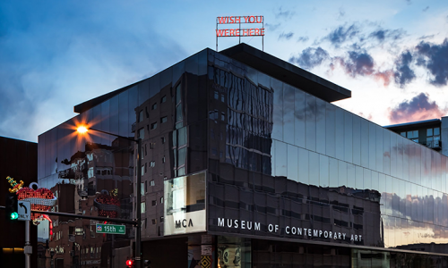 "Exterior shot of the Museum of Contemporary Art Denver at sundown. A neon sign in red is displayed on the buildings roof and reads ""WISH YOU WERE HERE."" The sunset is reflected on the buildings side."