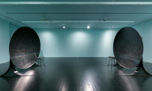 Image of a gallery where two large circular metal sculptures face each other about 10 feet apart. The room is bathed in a teal light and the lights reflect off the dark floor.