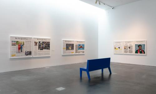 A white museum gallery with concrete floors. There are seven large, framed newspapers hung on the two walls. Near the center, there is a blue bench, and only the back of the bench is visible.