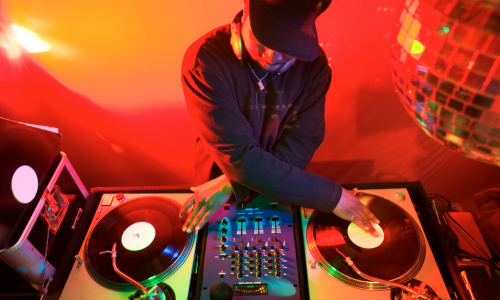 Image of a person with their head down in a black sweatshirt and black hat mixing on two turn tables. There are bright red lights surrounding him and a disco ball in the corner.