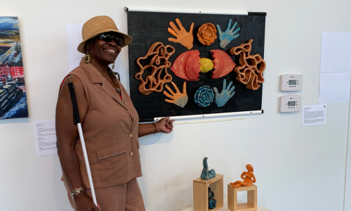 An African American woman dressed in all brown wearing sunglasses and a brown straw bucket hat, standing in what appears to be a gallery. They are next to multiple works of art, but specifically pointing at a three dimensional work that's hanging on the wall next to them.