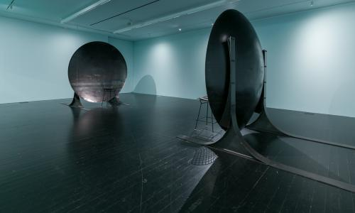 [Image description: An image of an art installation in a white gallery space. The work consists of two chairs, each sitting in front of their own large discs, which are meant to replicate the effects of an acoustic mirror. The discs reflect and focus sound waves in a way that visitors can sit far apart but will hear each other as if they are standing right next to each other.]