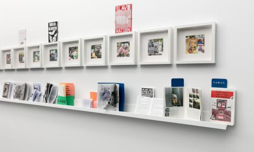 An image of a white wall in one of the MCA Denver galleries. Affixed to the wall are a series of white square frames: inside the frames are photographs of little neighborhood libraries. Underneath is a shelf with colorful zines with different images and graphics on them, with titles ranging from 'SLAVE NATION' to 'THE ART AND SCIENCE OF BILLBOARD IMPROVEMENT'.