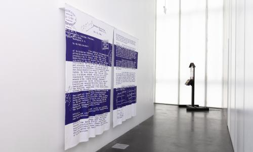 Artist Alan Michelson's, artwork of a reproduction of the December 30, 1924 letter to Calvin Coolidge by the chiefs of the Onondaga Nation, protesting the Indian Citizenship Act and reaffirming Onondaga sovereignty. The reproduction is on a pair of blankets in the colors white and purple and hangs on a white gallery wall with a dark concrete floor.