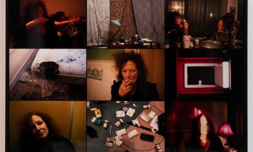 Close up image of Nan Goldin's work titled Memory Lost. There are nine landscape photographs of various scenes: hazy self-portraits captured as if underneath a red hue, pictures of carpets strewn with various pill bottles, along with other intimate, isolated scenes.