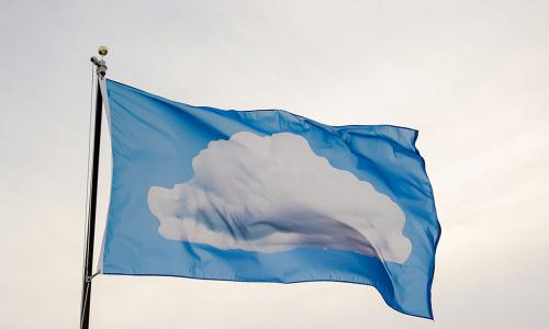 Sky blue flag against an overcast off white sky. The flag has a white cloud in the center.