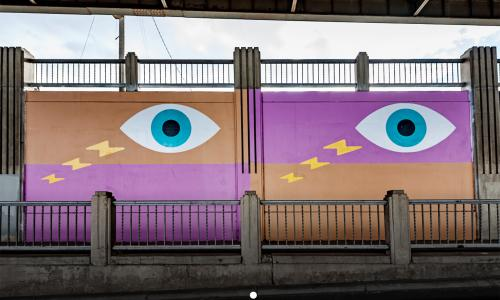 Image of aerosol and acrylic mural painting of wide eyes and lightning bolts, fuchsia and gold rectangular fields