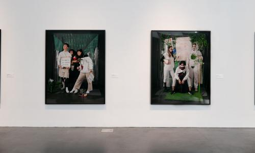 Image of four large blacked framed color prints of students posed in different portrait settings dressed in futuristic ideas with props