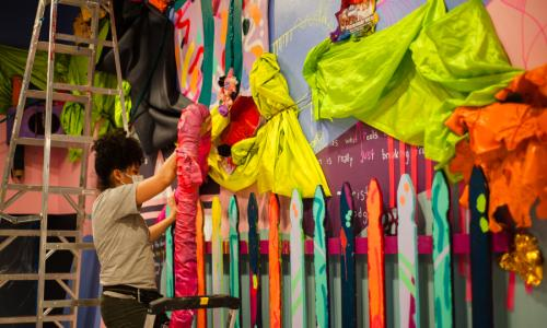 A brightly colored large scale, 3D collage installation, that displays a wide range of materials: a picket fence, cloth draped from and tied to the wall, large tube-like structures, and other thrifted materials. Artist Moe Gram is standing in front of the wall working on the installation. She is in gray jeans and a light gray t-shirt, with curls hanging down on her face. Behind her is a tall ladder.