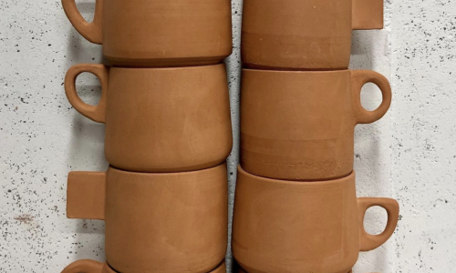 Two stacks of terra-cotta colored mugs waiting to be glazed. Each stack includes five mugs, and each mug has a different style handles on them. The mugs are sitting in front of a speckled black and white backdrop.