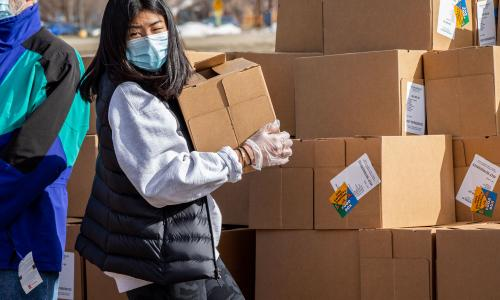 Image of a woman unloading boxes of donations