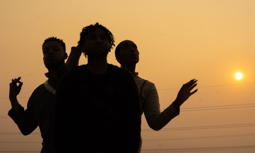 photo of the band. Silhouette of the band with a burning orange glow from the sunset behind them