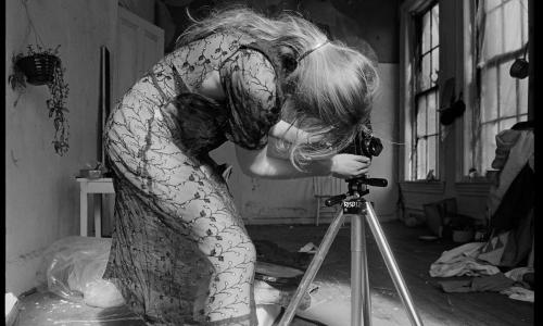 A woman is hunched over, her back facing the camera, in a sheer dress adjusting a camera on a tripod in a messy indoor space.
