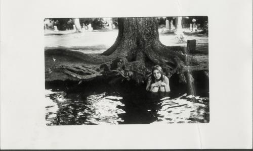 A woman sits in a pond with the base of a tree visible behind her. She has her knees to her chest and rests her hands upon her knees. She looks into the camera with a longing look on her face.